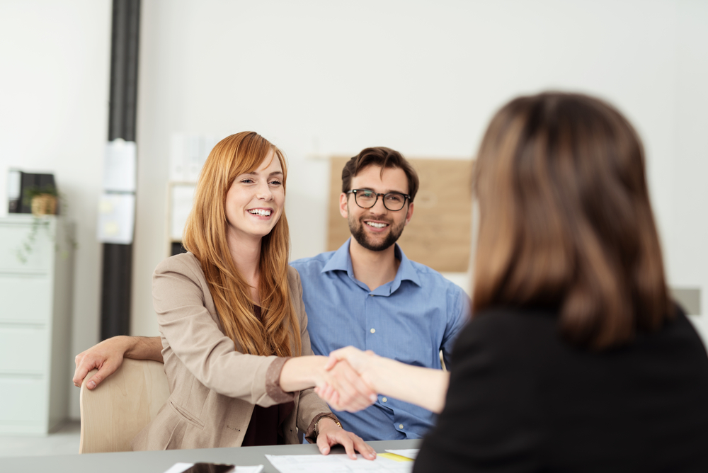 Happy young couple meeting with a broker in her office leaning over the desk to shake hands, view from behind the female agent