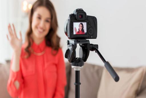 A woman recording video through camera
